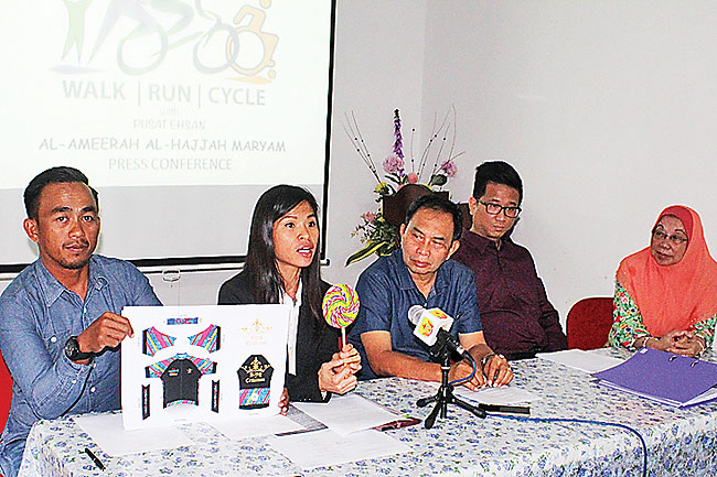 Mewsum Wong (second from left) explaining the design of the King of Criterium Cycling shirt. - ABDUL HAKIIM YAKOF