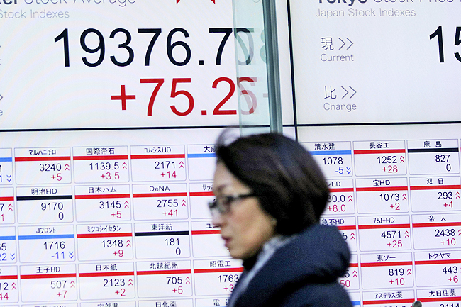 A woman walks past an electronic stock board showing Nikkei stock index at a securities firm in Tokyo. - AP