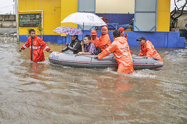 Flood-affected residents use a rubber boat in an inundated neighbourhood in Jakarta. - AFP