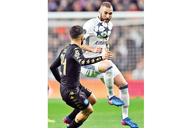 Real Madrid's French forward Karim Benzema vies with Napoli's midfielder Lorenzo Insigne during the match.