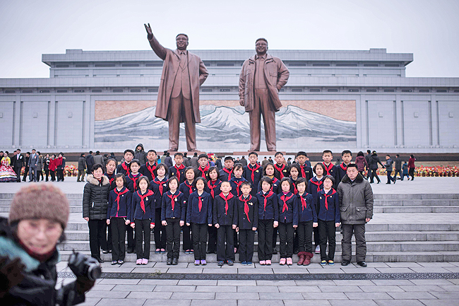 A group of children pose for a group photo as they visit the statues of late North Korean leaders Kim Il-Sung and Kim Jong-Il to pay their respects on the occasion of the 75th anniversary of the birth of Kim Jong-Il, at Mansudae hill in Pyongyang, on February 16. - AFP