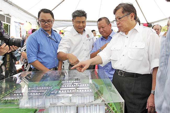 Sarawak Chief Minister Datuk Amar Abang Johari (right) looking at a housing model during the launch of the 1Malaysia Civil Servants Housing Project. - BERNAMA
