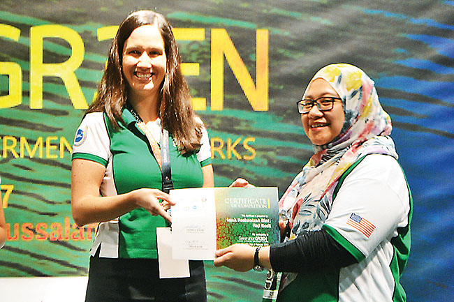 Catherine Muller, the Public Affairs Officer at the US Embassy in Brunei Darussalam presents a certificate to a participant