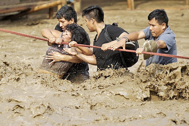 A group of people, stranded in floodwaters, hold onto a rope as they wade to safety in Lima, Peru. - AP