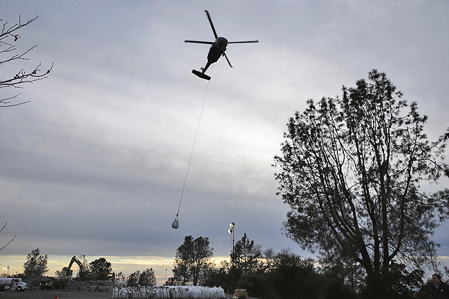 In this file photo, a helicopter takes off with a bag filled with rock to be dropped in a hole on the lip of the Oroville Dam's emergency spillway
