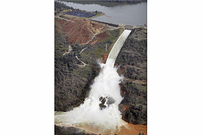 Water flows down the damaged spillway at Oroville Dam in California. - PHOTOS: AP