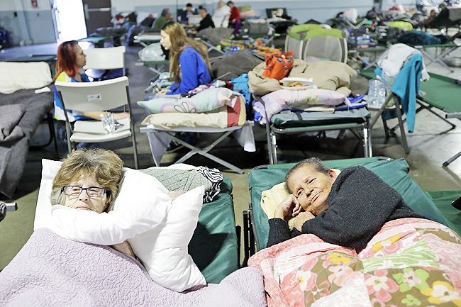 Delores Dearte (R) and Merna Thompson, neighbours from the town of Gridley, rest at a shelter for evacuees from cities surrounding the Oroville Dam, in Chico, California