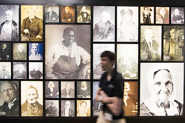 A person walks past a wall of photos of people born before the end of the American Revolution at the museum