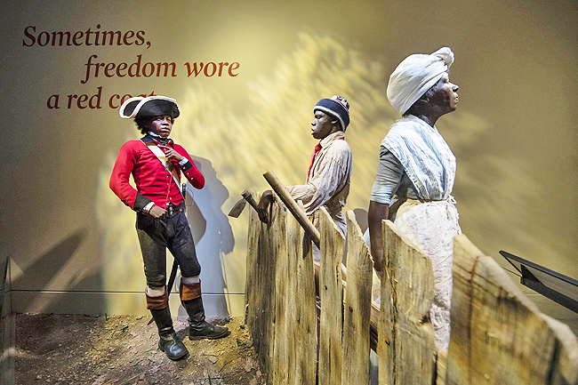 The display depicts a 14-year-old London Pleasant, left, who left slavery by joining a Loyalist regiment encouraging other slaves to flee to the British Army in search freedom