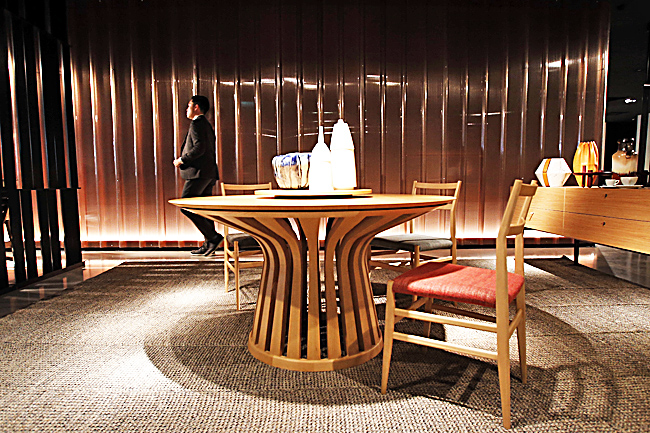 A man walks next to the round table called 'Lebeau' created by designer Patrick Jouin for Cassina's furniture designers, at the Cassina space