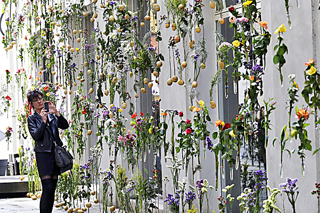 Photo taken on April 4 shows a woman taking a photo at a creation by Piuarch called 'Flowerprint'