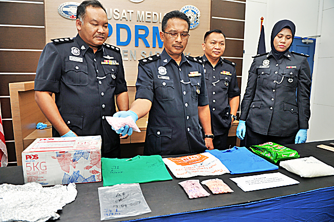 Sarawak Narcotic Criminal Investigation Department head Supt Sahar Abdul Latif (L) shows seized ecstasy pills and cocaine to reporters during a press conference at the Sarawak police contingent headquarters in Kuching yesterday. - BERNAMA