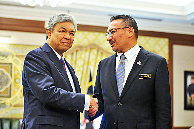 Malaysian Deputy Prime Minister Datuk Seri Dr Ahmad Zahid Hamidi (L) shakes hands with Defence Minister Datuk Seri Hishammuddin Tun Hussein, who is also the Minister of Special Functions, after a courtesy call by Hishammuddin at his office at Perdana Putra in Putrajaya yesterday. - BERNAMA