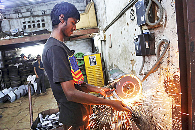 An Indian worker grinds metal to finish a part made for heavy vehicles at an industrial unit in Bangalore. - AP