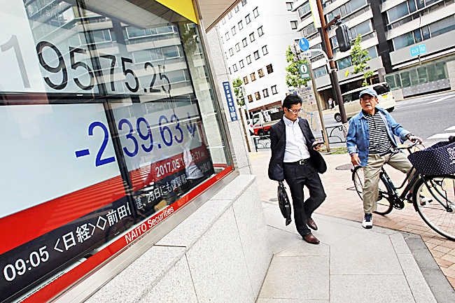 An electronic stock board shows Japan's Nikkei 225 index at a securities firm in Tokyo. - AP