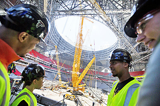 Cranes poke through the retractible roof under construction inside the Mercedes-Benz Stadium as rapper TI, left, tours the new stadium for the Atlanta Falcons NFL football team in Atlanta