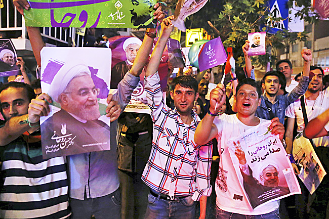 Supporters of Iranian President Hassan Rouhani cheer while holding his posters during a street campaign ahead of the presidential election in downtown Tehran. - AP