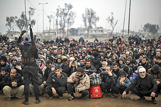 In this file photo, displaced Iraqis, fleeing fighting between security forces and IS militants, wait for a security check before being transferred to a camp on the western side of Mosul. - AP