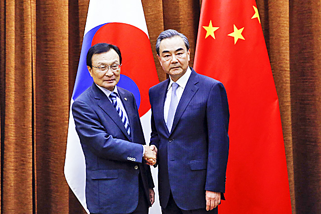 Chinese Foreign Minister Wang Yi (right),  shakes hands with South Korean special envoy Lee Hae-chan during a meeting at the foreign ministry in Beijing, China, yesterday. - AP