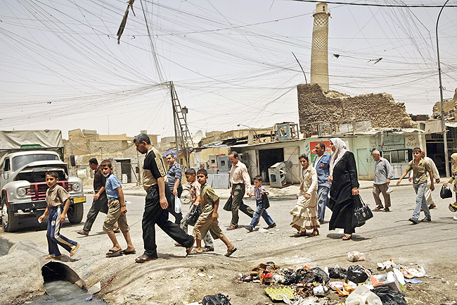 Residents walk past the tilted minaret of al-Nuri mosque in busy market area in Mosul, Iraq in this June 8, 2009 file photo. US-backed Iraqi troops pushed into the last Islamic State stronghold in the country's second largest city of Mosul yesterday, an Iraqi commander said, formally launching the final major battle of an eight-month campaign. - AP