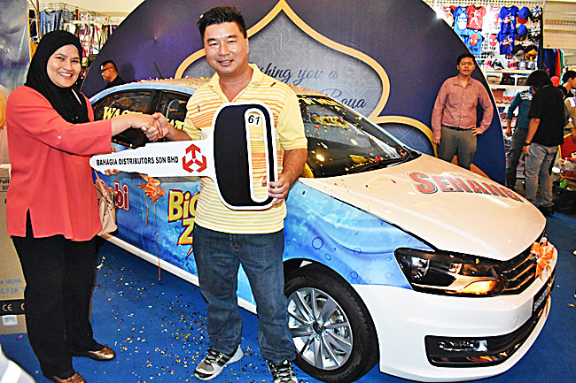 Grand prize winner Ngieng Chew Yong receiving the mock key for his Volkswagen Vento from Jarol, the representative of Southern Lion Sdn Bhd, Malaysia. - PHOTOS: D'SUNLIT