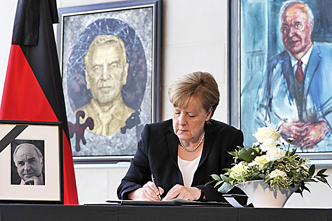 German Chancellor Angela Merkel signs a condolence book for former German Chancellor Helmut Kohl at the chancellery in Berlin, Germany. - AP