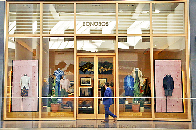 A man walks by the Bonobos Guideshop in New York's Financial District. - AP