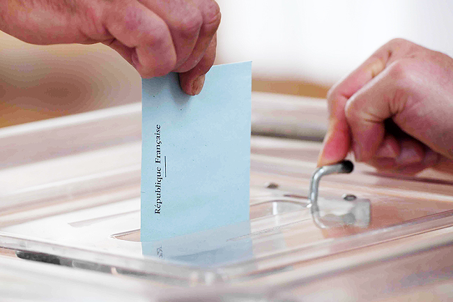 A person casts a ballot at a polling station during the second round of the French parliamentary elections. - AFP