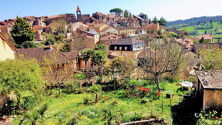 A hilltop village in the Dordogne River region of France, as seen from a backyard garden
