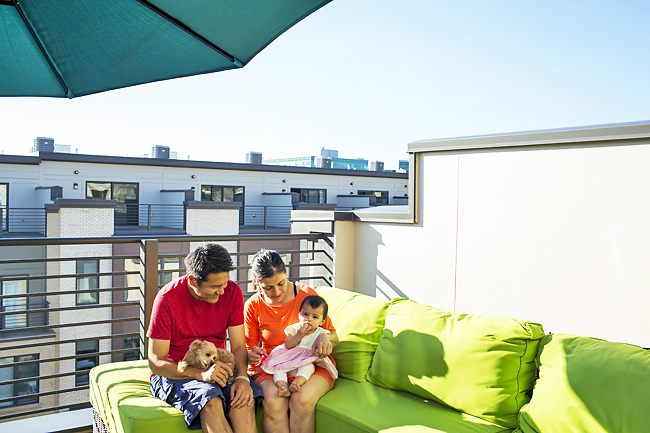 Keisuke and Idalia Yabe, who bought a townhouse at Montgomery Row, a development in the Rock Spring Park office complex in North Bethesda, Maryland, sit on their rooftop with their daughter, Mela, and their dog. - PHOTOS: WP-BLOOM