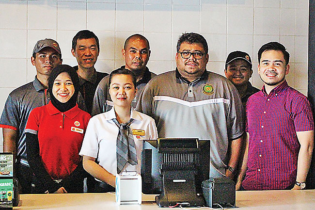 Burger King Brunei Marketing Managers Izam Ahmad (R) and Lim Kai Wei (3rd L) pose for a photo with BFL 2017 Chairman Rosdin Abdul Aziz (3rd R), BFL 2017 Secretariat Bahmin Haji Ahmad (4th R) and Burger King Brunei staff at Burger King's restaurant in Citis Square. - KHAIRIL HASSAN