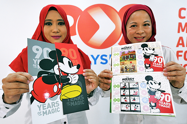 Malaysian Stamp And Philately Head Diyana Lean Abdullah Pos Malaysia Staff Noraini Mohd Salleh Show Mickey Mouses To Celebrate