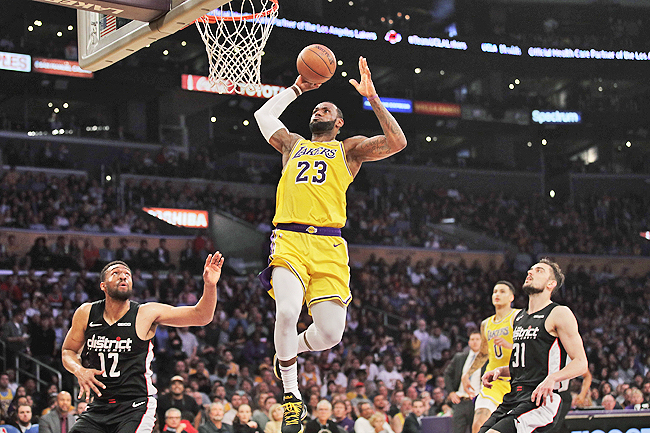 """f3ffe60b345a Los Angeles Lakers  LeBron James (C) goes up for a dunk as Washington  Wizards  Jabari Parker and Tomas Satoransky look on. – AP. """""""